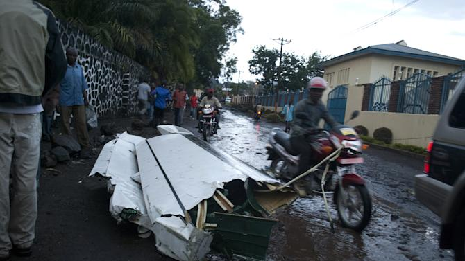 A motorcyclist drives past a piece of a plane wing lying in a road in central Goma, Congo, at a distance of several hundred meters from the main crash site, Monday, March 4, 2013. A Fokker airplane of the private airline CAA crashed in the city center Monday, killing at least six people onboard. There were no reported casualties on the ground.(AP Photo/Sinziana Demian)