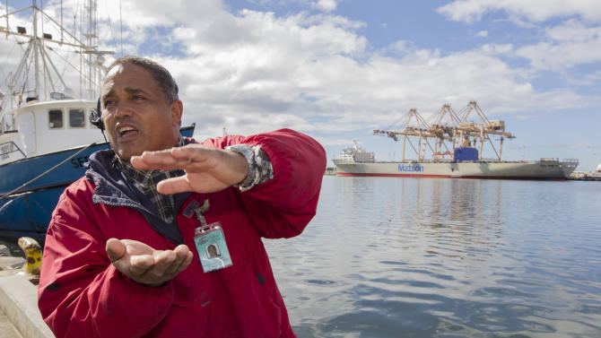 John Hernandez of Kailua, Hawaii and owner of John's Fresh Fish, describes the effect of the spilled molasses will have on the marine like in Honolulu Harbor and near by Keehi Lagoon Thursday, Sept. 12, 2013, in Honolulu. Off to the right in the back ground is the Matson container ship Mahi Mahi which is being loaded at the Matson container base yard's pier 52. A pipe maintained by Matson at pier 52 cracked and leaked about 233,000 gallons of molasses into the harbor. The molasses spill is being blamed for the killing of marine life at Keehi Lagoon which is located near the Honolulu Harbor. The cracked pipe has been repaired and the molasses leak stopped. (AP Photo/Eugene Tanner)