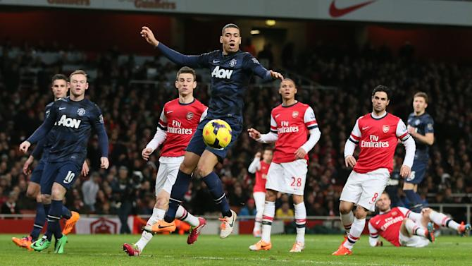 Manchester United's Chris Smalling, centre, watches as the ball goes past and he misses an chance on goal during their English Premier League soccer match between Arsenal and Manchester United at the Emirates stadium in London, Wednesday, Feb. 12, 2014. (AP Photo/Alastair Grant)