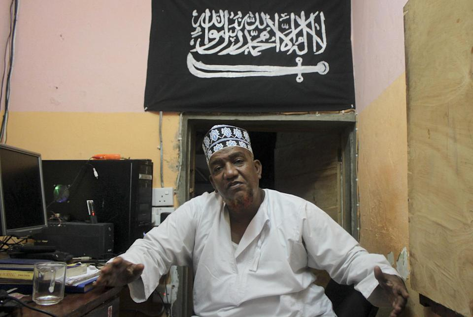 In this photo taken Tuesday, Oct. 29, 2013, Abubakar Shariff Ahmed, an influential member of a controversial mosque where two previous mosque leaders were killed under mysterious circumstances, sits in his office in Mombasa, Kenya. Writing in Arabic on islamist flag reads