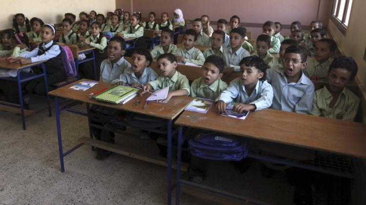 Students attend a class on the first day of their new school year at a government school in Giza
