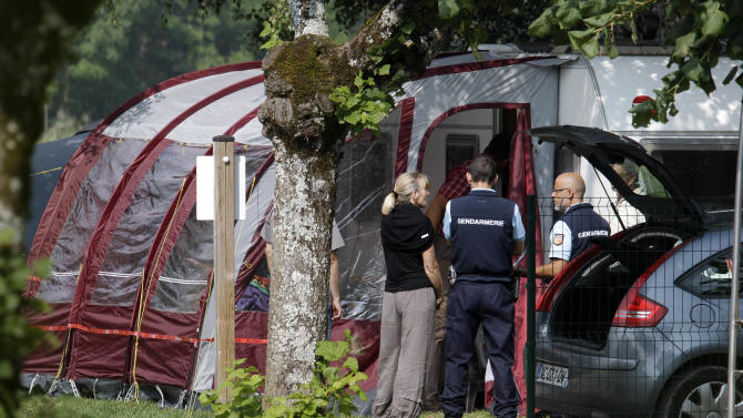 Gendarmes and investigators stand at the camp site where the slain British family were holidaying in Saint Jorioz, near Annecy, Thursday, Sept. 6, 2012. Immobilized with fear, a 4-year-old British girl huddled for eight hours beneath the legs of her slain mother in the back of a car filled with corpses on a remote Alpine road — all while French investigators stood nearby, unaware the girl was there. The stunning discovery Thursday of the girl, apparently unharmed, heightened the drama around a mysterious shooting rampage that left four adults dead and a 7-year-old girl hospitalized with bullet wounds and skull fractures. The reason for the killing, in a wooded area near the village of Chevaline, remains unclear.   (AP Photo/Lionel Cironneau)