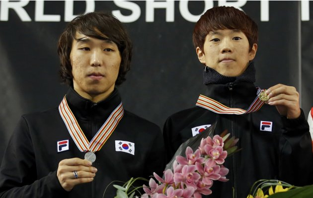 Second placed Kim of South Korea and winner compatriot Sin show their medals on the podium after the men's 1500m finals at the ISU World Short Track Speed Skating Championships in Debrecen