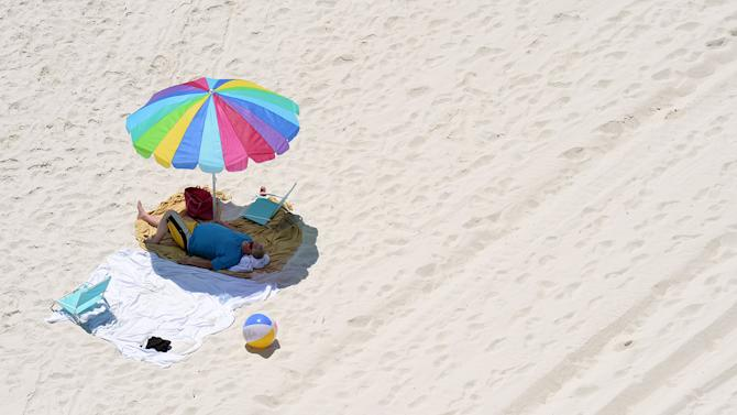 A beach goer enjoys the shade in Panama City Beach, Fla. on Thursday, May 7, 2015.  The beach is a popular location for Spring Break. (Andrew Wardlow/The News Herald via AP)