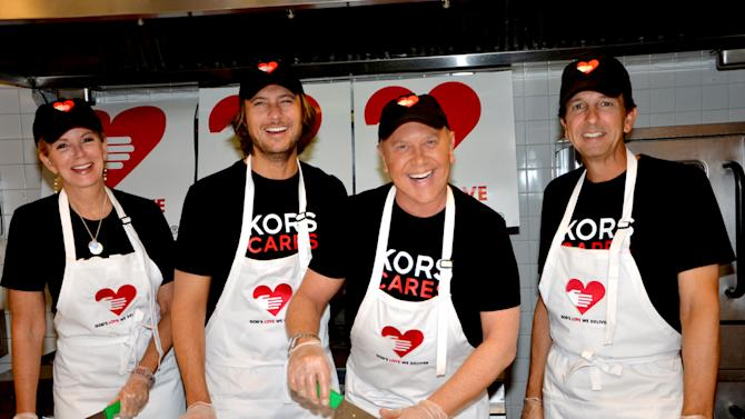 This undated image released by Michael Kors shows, from left, Blaine Trump, Lance Le Pere, Michael Kors and John Idol at Kors' annual volunteering for God's Love We Deliver in New York. Michael Kors knows a few things about getting his message out. On Wednesday, Oct. 16, 2013, Kors embarks on a new campaign: World Hunger Day. (AP Photo/Michael Kors)