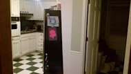 View of the hallway and side of refrigerator in old kitchen