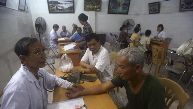 In this photo taken on March 18, 2013, patients at the Scientology Health Center of the Vietnam Association of Orange Victims get their pulse and blood pressure checked by doctors in Thai Binh, Vietnam. The center runs a 25-day health program which, as well as massive consumption of vitamins, includes four-hour sauna sessions and a morning run. While there is no medical evidence that the treatment at the center is effective, Vietnamese authorities are supporting it as a way of relieving some of the suffering of the between 2 and 4 million people suffering from illnesses linked to exposure to Agent Orange during the war. (AP Photo/Na Son Nguyen)