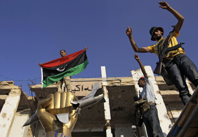 Rebel fighters gesture as one of them stands on a monument inside Moammar Gadhafi's main compound in Bab Al-Aziziya in Tripoli, Libya, Tuesday, Aug. 23, 2011. Libyan rebels stormed Moammar Gadhafi's main military compound in Tripoli Tuesday after fierce fighting with forces loyal to his regime that rocked the capital as the longtime leader refused to surrender despite the stunning advances by opposition forces. (AP Photo/Sergey Ponomarev)