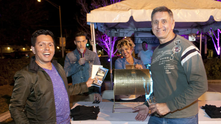 Roberto Paniagua, left, and George Hasandras, right, won one of the many prizes in a raffle at the Wilton Manors Out of the Closet (OTC) Block Party & Insti-Test Launch Marking the 5th anniversary of Wilton Manors OTC in Wilton Manors, Florida on Saturday, February 2nd, 2013 at the Hagan Park/City Hall parking lot in Wilton Manors, FL. (Mitchell Zachs /AP Images for AIDS Healthcare Foundation)