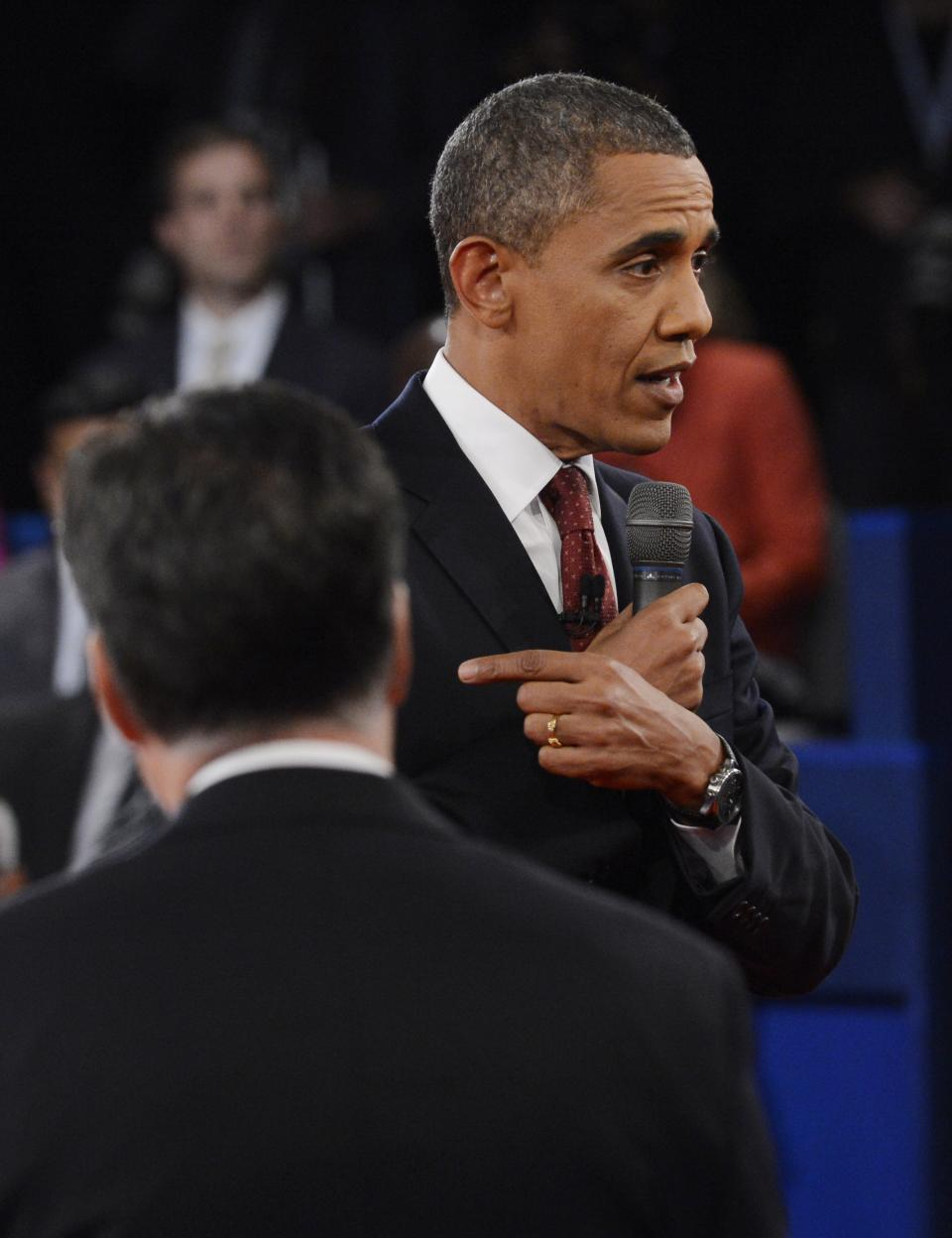 Republican presidential nominee Mitt Romney, left, listens as President Barack Obama addresses members of the audience during the second presidential debate at Hofstra University, Tuesday, Oct. 16, 2012, in Hempstead, N.Y. (AP Photo/Pool-Michael Reynolds)