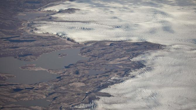 This July 26, 2011 aerial photo shows the edge of the Greenland ice sheet, right, adjacent to a series of lakes in central Greenland. (AP Photo/Brennan Linsley)