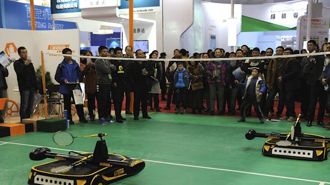 People look on as a robot plays badminton with a boy during a demonstration at the World Robot Conference in Beijing