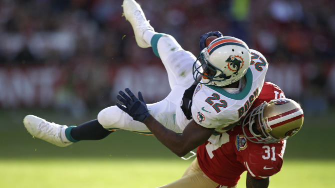 Miami Dolphins running back Reggie Bush, left, is stopped with the ball by San Francisco 49ers strong safety Donte Whitner, right, during the third quarter of an NFL football game in San Francisco, Sunday, Dec. 9, 2012. (AP Photo/Ben Margot)