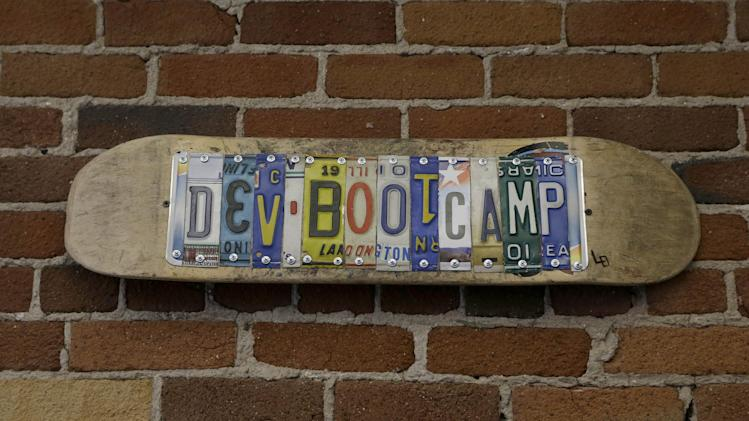"""A sign for Dev Bootcamp is shown at their office in San Francisco, Tuesday, April 2, 2013. Dev Bootcamp is one of a new breed of computer-programming schools that's proliferating in San Francisco and other U.S. tech hubs. These """"hacker boot camps"""" promise to teach students how to write code in two or three months and help them get hired as web developers, with starting salaries between $80,000 and $100,000, often within days or weeks of graduation. (AP Photo/Jeff Chiu)"""