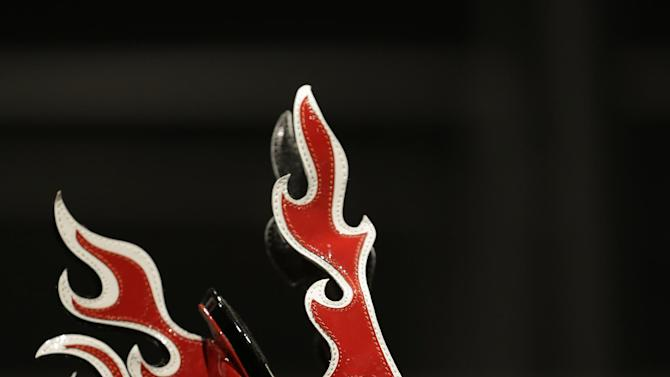 """This Feb. 11, 2013 photo shows a red and white patent leather flame Prada sandal displayed at the """"Shoe Obsession"""" exhibit at The Museum at the Fashion Institute of Technology Museum in New York. The exhibition, showing off 153 specimens, runs through April 13. (AP Photo/Kathy Willens)"""