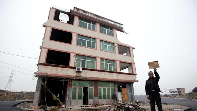 Luo Baogen holds his land certificate as he stands next to his house in the middle of a newly built road in Wenling city in east China's Zhejiang province Thursday, Nov. 22, 2012. Luo, the owner of the house, refused to sign an agreement to allow his house to be demolished by the authorities, as the compensation offered to him was not enough, according to local media. (AP Photo)