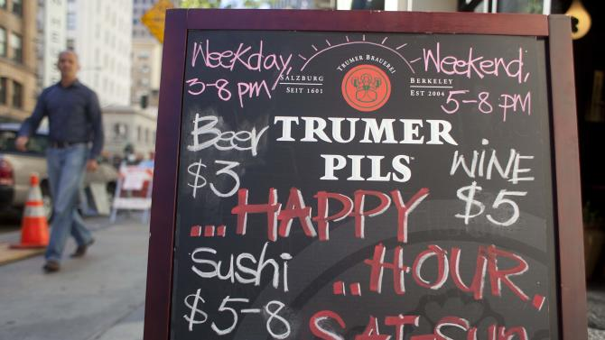 In this photo taken Monday, Aug. 6, 2012, a  man walks past a sign advertising a happy hour at a restaurant on Second Street in San Francisco.  The concept of happy hour when bars offer lower prices or two-for-one specials seems like a widespread tradition, but is actually illegal or restricted in quite a few places. (AP Photo/Eric Risberg)