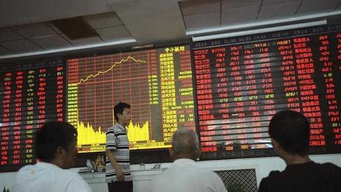 An investor walks past as others look at an electronic board showing stock information at a brokerage house in Wuhan