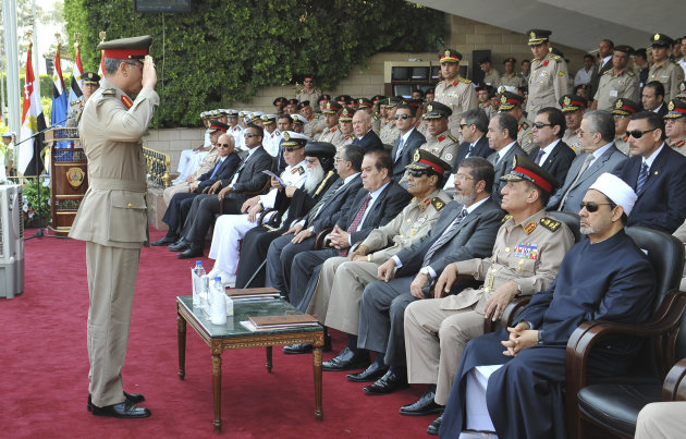 In this image released by the Egyptian President, an Egyptian military officer salutes President Mohammed Morsi, third from right, as he sits with Prime Minister Kamal el-Ganzouri, center, Field Marshal Hussein Tantawi, fourth right, Army Chief of Staff Gen. Sami Anan, second right, and the Grand Sheik of Al-Azhar, Ahmed el-Tayyib, right, at a graduation ceremony at a military base east of Cairo, Egypt, Monday, July 9, 2012. Egypt's highest court insisted Monday that its ruling that led to the dissolution of the Islamist-dominated parliament was final and binding, setting up a showdown with the country's newly elected president. The announcement on state TV came a day after President Mohammed Morsi recalled the legislators, defying the powerful military's decision to dismiss parliament after the Supreme Constitutional Court ruled that a third of its members had been elected illegally.(AP Photo/Sheriff Abd El Minoem, Egyptian Presidency)