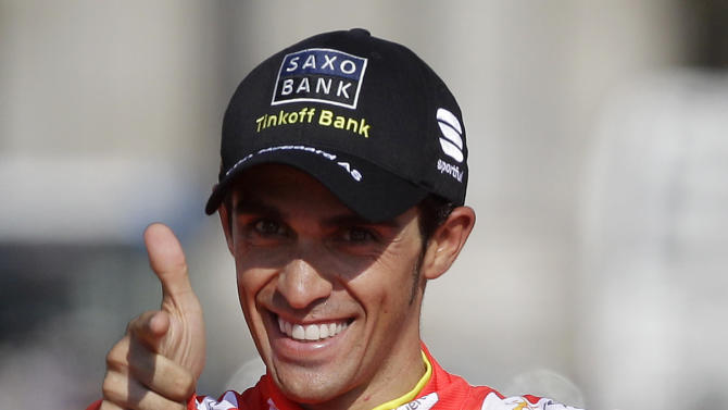 Saxo Bank Team cyclist Alberto Contador celebrates at the podium his victory on the Spanish Vuelta cycling race after riding the final stage along 115 km (71 miles) from Cerdedilla to Madrid, on Sunday, Sept. 9, 2012.  This is the second time Contador wins the Spanish vuelta, who also has a pair of Tour de France and one Giro d'Italia.  (AP Photo/Alberto Di Lolli)