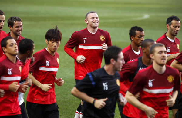 Manchester United's Wayne Rooney, center background, warms up with ...