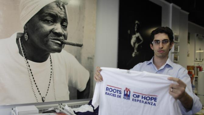 "Moas holds a t-shirt of his organization ""Roots of Hope"" in Miami Beach"