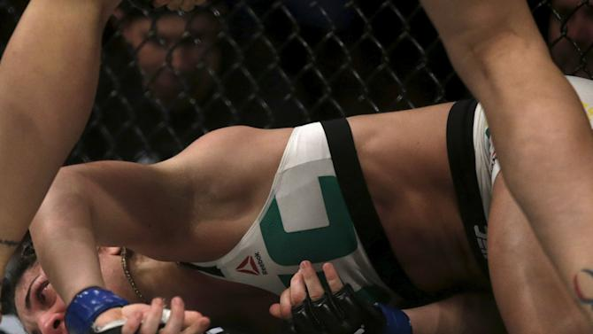 Correia of Brazil lies on the ground after receiving a punch of Rousey of U.S during their UFC match in Rio de Janeiro
