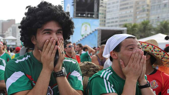 Mexico soccer fans react after a second goal was scored against their team as they watch the World Cup round of 16 match against Netherlands on a live telecast inside the FIFA Fan Fest area on Copacabana beach in Rio de Janeiro, Brazil, Sunday, June 29, 2014. The Netherlands staged a dramatic late comeback, scoring two goals in the dying minutes to beat Mexico 2-1 and advance to the World Cup quarterfinals. (AP Photo/Leo Correa)