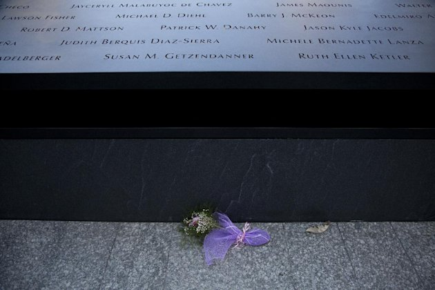 Flowers lay at the base of the south reflecting pool before tenth anniversary ceremonies of the terrorist attacks at the site of the World Trade Center, Sunday, Sept. 11, 2011, in New York. (AP Photo/