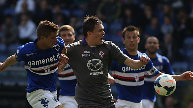 Sampdoria defender Gaetano Berardi, left, challenges Fiorentina midfielder Josip Ilicic during a Serie A soccer match in Genoa, Italy, Sunday, March 30, 2014