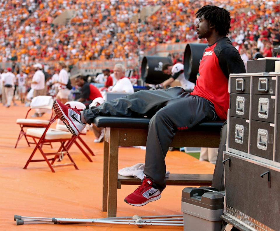 Georgia's Keith Marshall, right, sits on a training table during an NCAA college football game against Tennessee in Knoxville, Tenn., Oct. 5, 2013. (AP Photo/Atlanta Journal-Constitution, Jason Getz)