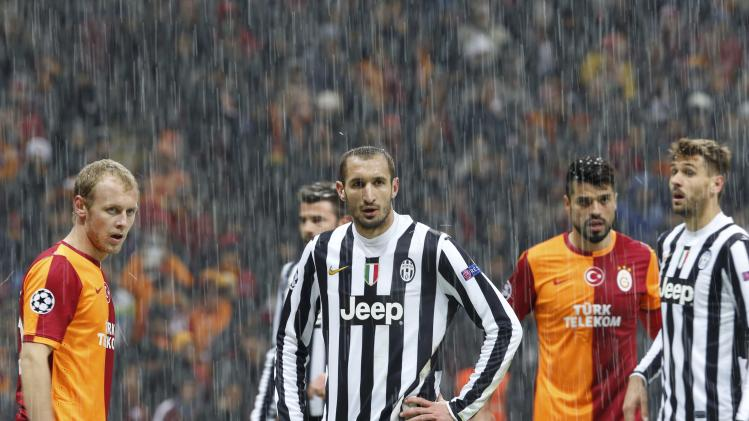 Players of Galatasaray and Juventus react as their match is paused for 20 minutes due a heavy snowfall during their Champions League soccer match in Istanbul