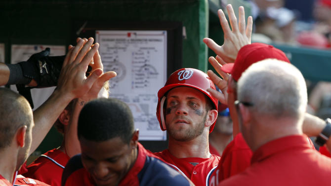 Washington Nationals' Bryce Harper, center, celebrates with his teammates after scoring during the sixth inning of a baseball game against the Colorado Rockies on Saturday, July 7, 2012 in Washington. The Nationals won 4-1. (AP Photo/Alex Brandon)