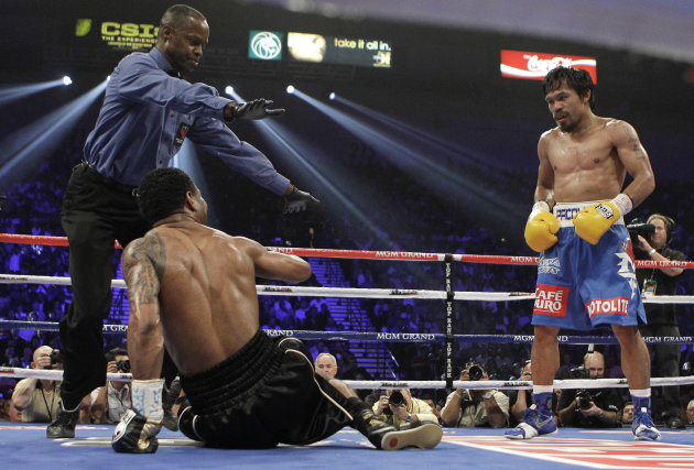 Manny Pacquiao, right, looks down at Shane Mosley who slipped during the fourth round as referee Kenny Bayless looks on during a WBO welterweight title bout, Saturday, May 7, 2011, in Las Vegas.  (AP
