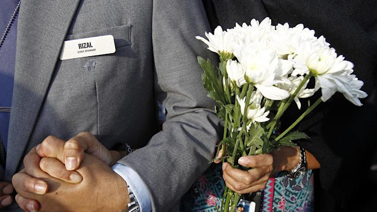 A Malaysia Airlines crew member holds flowers as she waits outside Bunga Raya Complex at Kuala Lumpur International Airport where victims' bodies of the ill-fated Malaysia Airlines Flight MH17 are scheduled to be flown back, in Sepang, Malaysia, Friday, Aug. 22, 2014. (AP Photo/Lai Seng Sin)