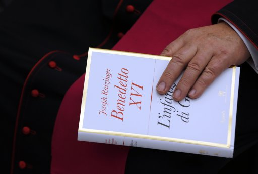 "Bishop holds a copy of Pope Benedict XVI's book ""The Childhood of Jesus"" during a presentation in Vatican"