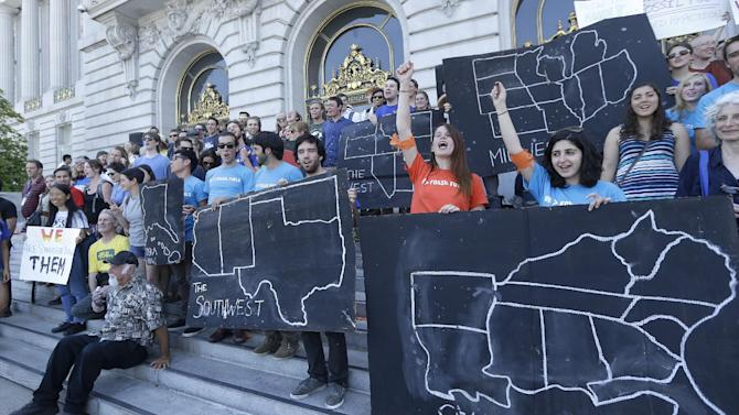 College students and supporters hold up signs at a rally to support fossil fuel divestment outside of City Hall in San Francisco, Thursday, May 2, 2013. In an effort to slow the pace of climate change, students at more than 200 colleges are asking their schools to stop investing in fossil fuel companies. (AP Photo/Jeff Chiu)