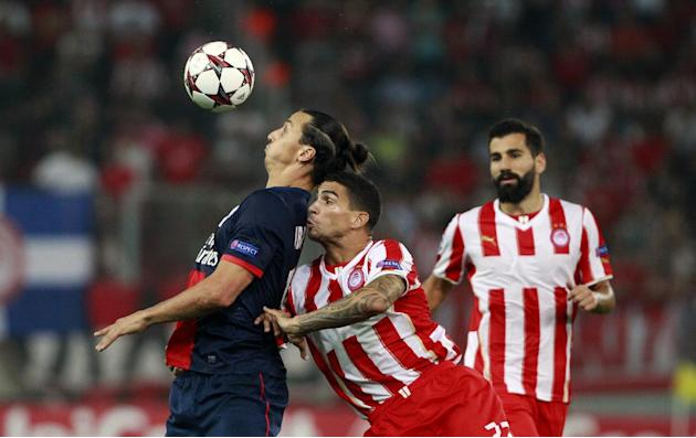 Paris Germain's Zlatan Ibrahimovic, left, and Olympiakos'  Carl Medjani, center, fight for the ball, during the soccer Champions League group C match between Olympiakos and Paris Saint Germain in Pira