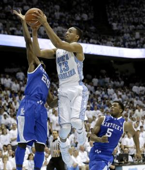 North Carolina's J.P. Tokoto (13) drives to the basket as Kentucky's Dominique Hawkins (25) and Andrew Harrison (5) defend during the first half of an NCAA college basketball game in Chapel Hill, N.C., Saturday, Dec. 14, 2013. (AP Photo/Gerry Broome)