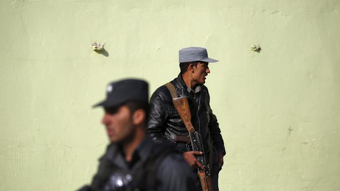 Afghan police keep watch near the site of a suicide blast in Kabul