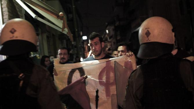 Protester holds a banner in front of a riot police cordon during an anti-fascist rally to mark the anniversary of the killing of Greek rapper Fyssas in a suburb of Athens
