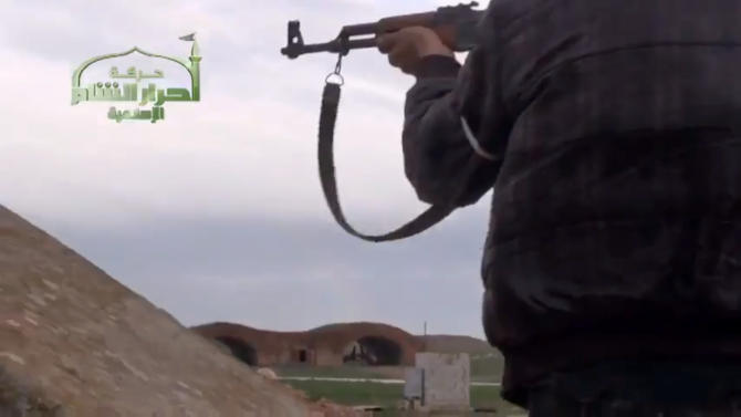 This image taken from video obtained from Ugarit News, which has been authenticated based on its contents and other AP reporting, shows Syrian rebels at Jarrah airfield in Aleppo province, Tuesday, Feb. 12, 2013. Rebels captured the military air base in northern Syria on Tuesday, their second major strategic victory in as many days, activists said. (AP Photo/Ugarit News via AP video)