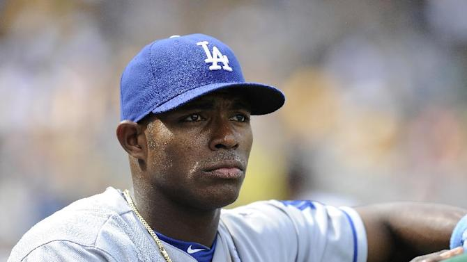 FILE - In this June 16, 2013, file photo, Los Angeles Dodgers right fielder Yasiel Puig watches from the in the dugout during the fourth inning of a baseball game against the Pittsburgh Pirates in Pittsburgh. The Florida Highway Patrol says that Puig has been arrested and charged with reckless driving on Saturday, Dec. 28, 2013, after officers clocked him driving 110 mph in a 70 mph zone. (AP Photo/Don Wright, File)