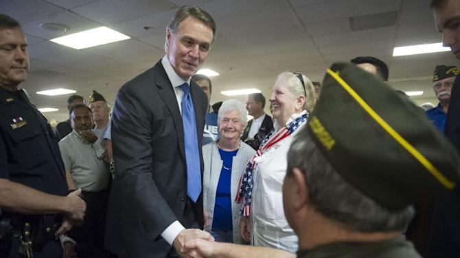 FILE - In this Oct. 15, 2014, file photo, Republican U.S. Senate candidate David Perdue, center, is greeted by Vietnam war veteran Ronnie Rogers as he campaigns in Marietta, Ga. Democrats are hoping to pull an upset in Georgia after GOP Senate nominee David Perdue has had to spend weeks defending his business record. Perdue has run as a former corporate executive with the experience necessary to help boost the economy. But Democrat Michelle Nunn for weeks has hammered Perdue as an overpaid CEO who mistreated employees. (AP Photo/John Amis, File)