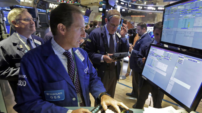 Specialist Glenn Carell, foreground, works with traders at his post that handles Twitter, on the floor of the New York Stock Exchange, Wednesday, July 29, 2015. Twitter sank 10 percent after reporting sluggish customer growth. (AP Photo/Richard Drew)