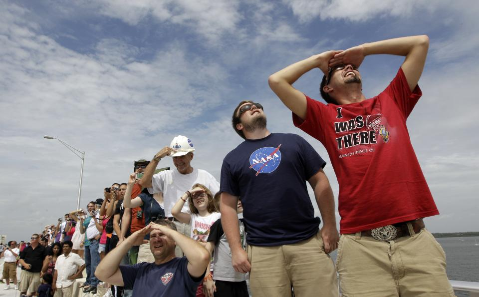 Russell Brawley, right, of Billings, Mont., watches as space shuttle Atlantis lifts off Friday, July 8, 2011, in Titusville, Fla. Four astronauts are taking space shuttle Atlantis for one last ride, the very last one of the 30-year space shuttle era. (AP Photo/David J. Phillip)