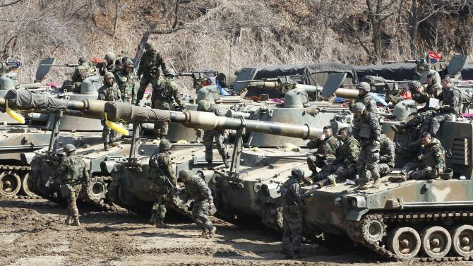 "South Korean marines take a rest on their K-55 self-propelled howitzers during an exercise against possible attacks by North Korea near the border village of Panmunjom in Paju, South Korea, Thursday, March 14, 2013. The body that controls North Korea's military dismissed new South Korean President Park Geun-hye, the first woman to hold the office, with a sexist reference Wednesday to the ""venomous swish"" of her skirt. (AP Photo/Ahn Young-joon)."