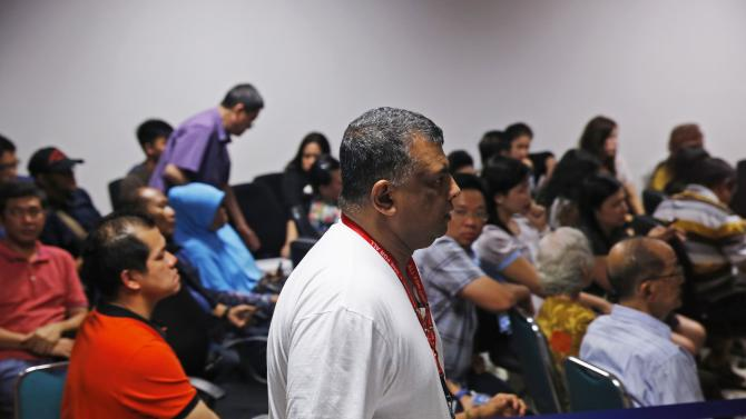 AirAsia CEO Tony Fernandes walks in front of family members of passengers onboard the missing AirAsia Flight QZ8501 at a news conference in Juanda International Airport, Surabaya