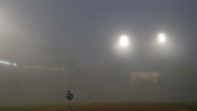 Toronto Blue Jays right fielder Jose Bautista leaves the field after a fog delay is called by the umpire crew during the third inning of a baseball game between the Chicago White Sox and the Blue Jays Monday, June 10, 2013, in Chicago. (AP Photo/Charles Rex Arbogast)