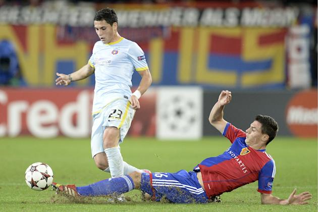 Steaua's Nicolae Stanciu, left, fights for the ball against Basel's Fabian Schaer, during a Champions League group E group stage match between Switzerland's FC Basel 1893 and Romania's FC Steaua Bucha